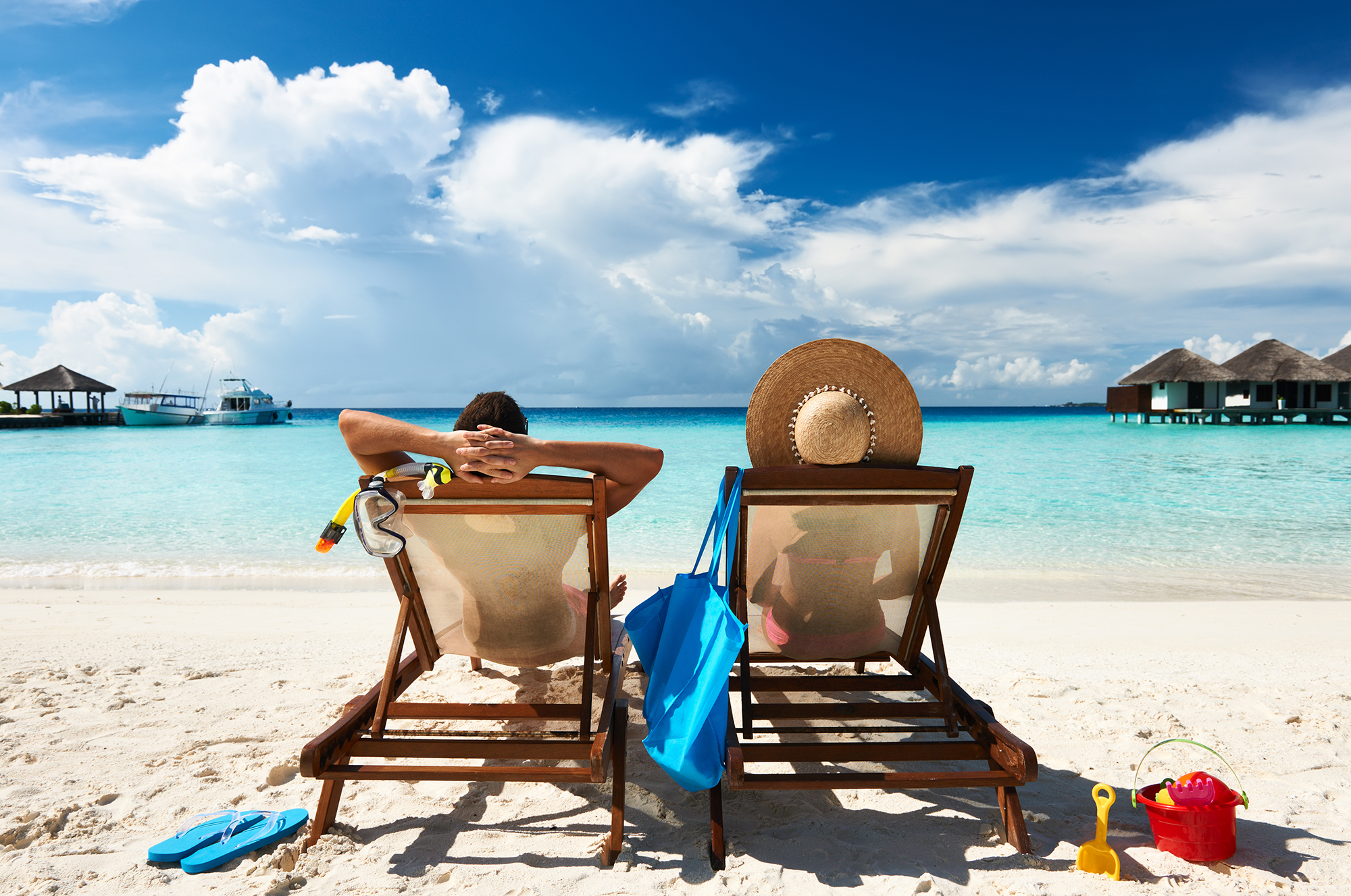 Two people relaxing on white sandy beach.
